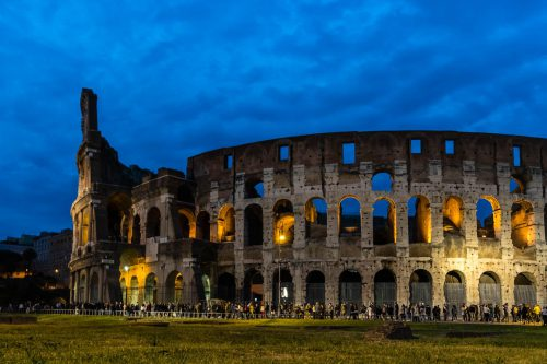 The colloseum by evening, still lines of people waiting to enter.