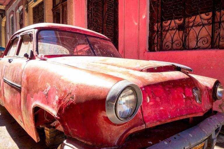 Rose klassieke auto voor de deur van gekleurd pand