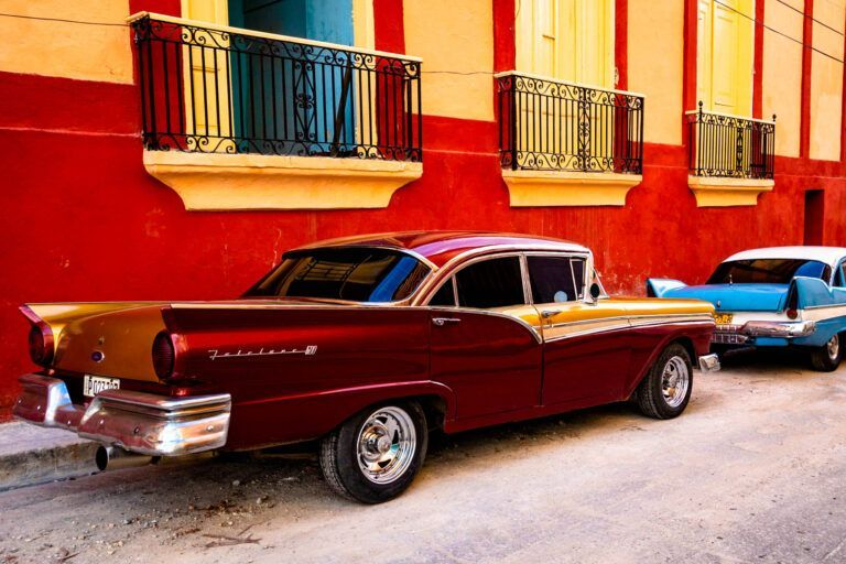 Beautiful cars in Santiago de Cuba matching colors with the houses shot in golden hour